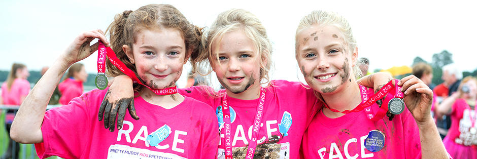 Three girls with medals after doing Pretty Muddy Kids