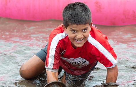 Boy crawling through mud in Pretty Muddy Kids