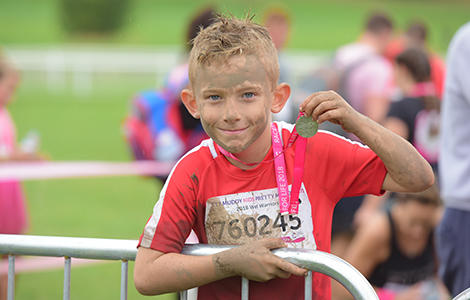 Boy with a medal after taking part in Pretty Muddy Kids