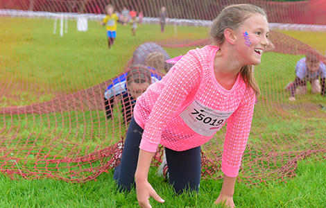 Girls crawling under netting in Pretty Muddy Kids obstacle course